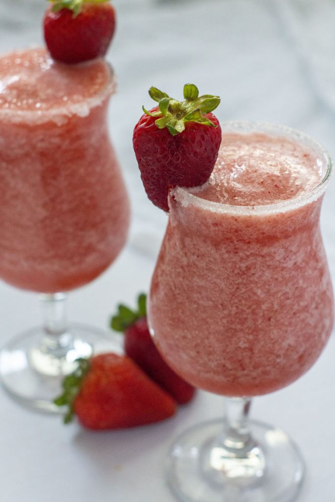 Strawberry Pineapple Daiquiri in glass with strawberry garnish (vertical)