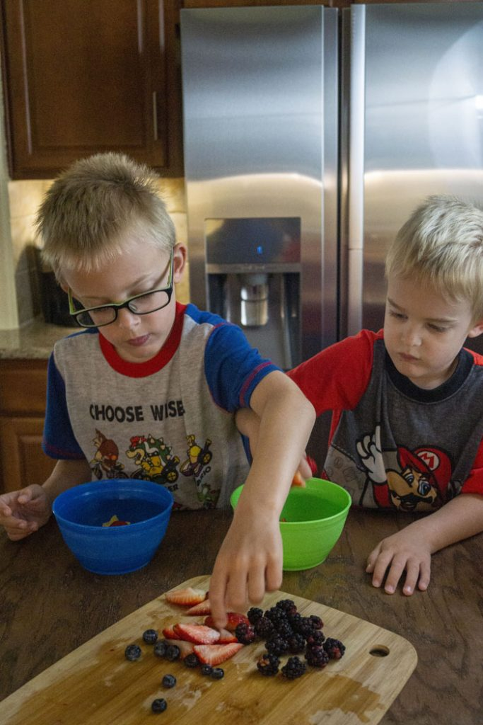 Two young boys placing berries in plastic bowls to make yogurt parfaits