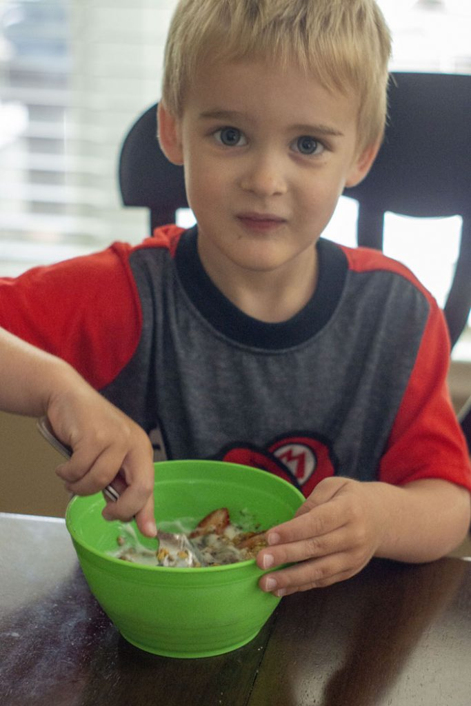 Young boy eating a yogurt parfait from a green bowl