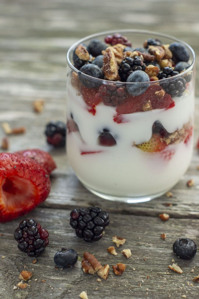 Yogurt in a glass with fruit and chopped nuts on a wooden background with ingredients around it (vertical)