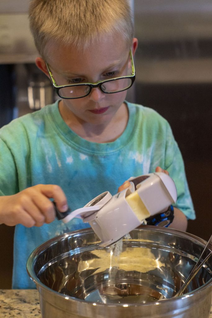 Young boy using a cheese grater to shred mozzarella cheese
