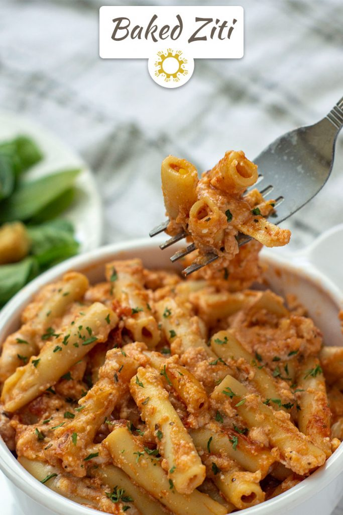 A bite of Baked Ziti in a white bowl being lifted by a fork (with title overlay)