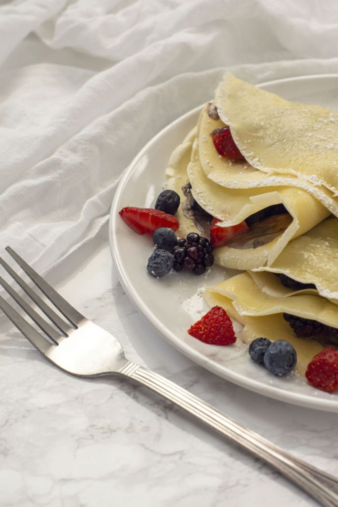 Multiple breakfast crepes filled with chocolate sauce and berries and garnished with powdered sugar on a white plate with a white napkin behind and a fork near the front on a grey marbled surface (vertical)