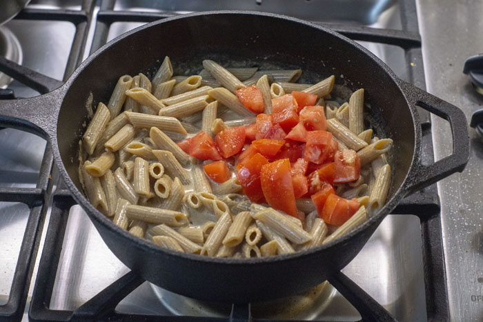 Cooked pasta noodles and chopped red bell pepper added to the cast iron skillet with cream over a gas stovetop