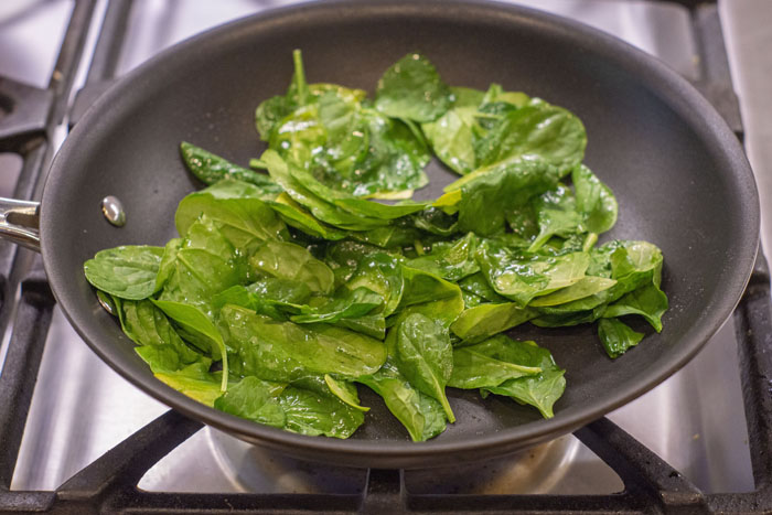 Small skillet with spinach leaves and olive oil over a gas stovetop