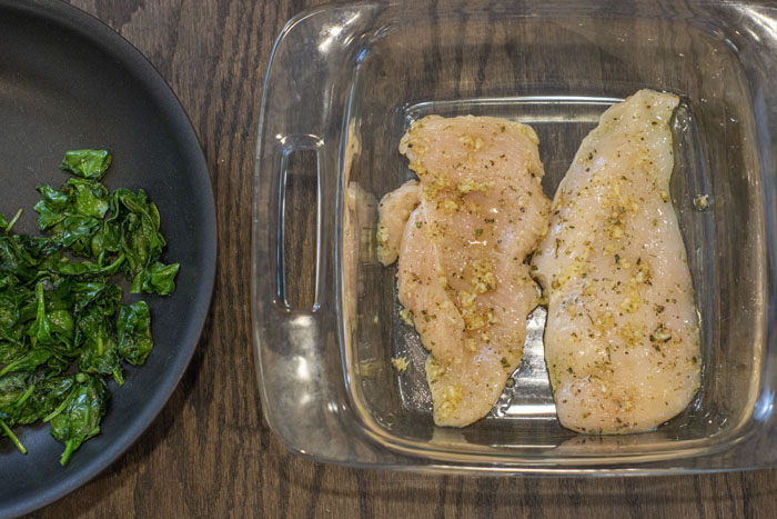 Glass baking dish with chicken breast to the right of the pan with wilted spinach leaves on a wooden surface