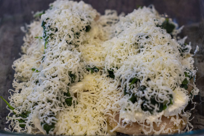 Close up of chicken covered with cream cheese, wilted spinach, and shredded mozzarella cheese on a wooden surface