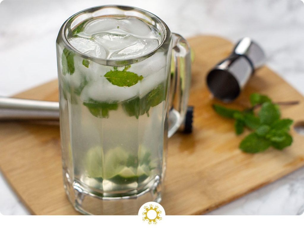 Classic Mojito in a beer mug on a wooden board with a muddler, measuring cup, and mint leaf (with logo overlay)
