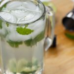 Classic Mojito in a beer mug on a wooden board with a muddler, measuring cup, and mint leaf (with title overlay)
