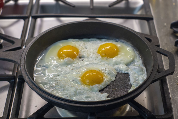 Three eggs being fried in a cast-iron skillet