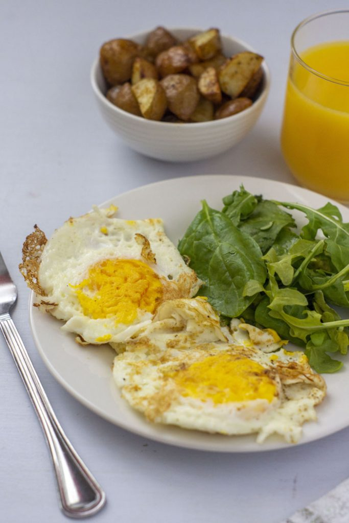 Fried Eggs Over-Hard on a white plate next to greens with breakfast potatoes and orange juice in the background (vertical)