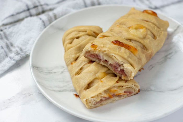 Salami and cheese hot pocket on a white and grey marbled plate