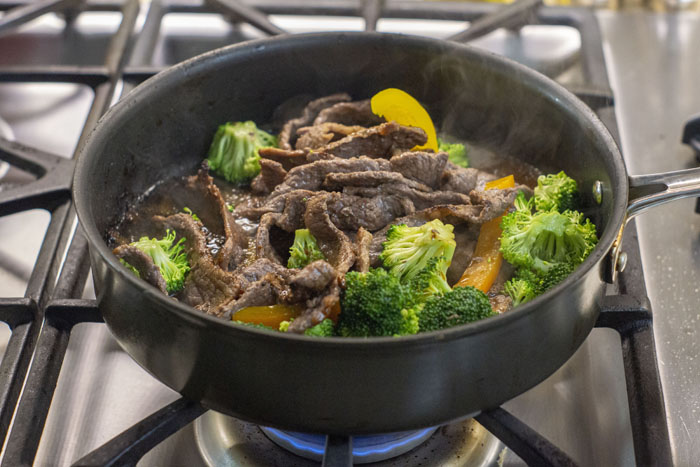 Large skillet on a gas stovetop with browned beef strips, chopped broccoli and bell peppers, and Mongolian sauce