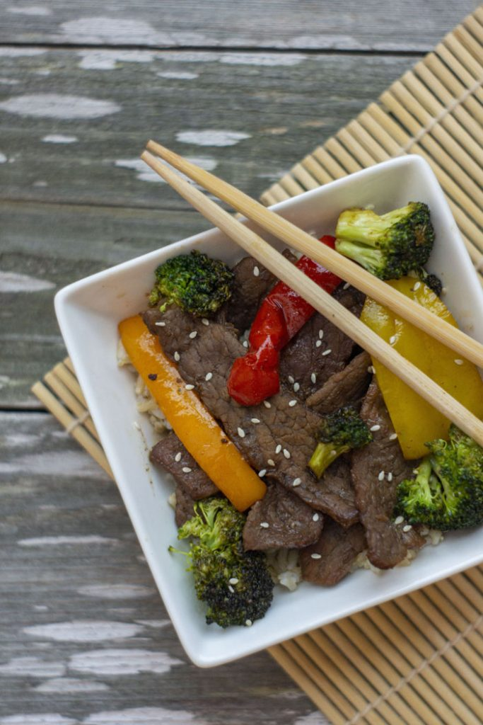 Top-down of Mongolian Beef Stir-Fry in a square white bowl with chop sticks on a wooden surface with a bamboo placemat (vertical)