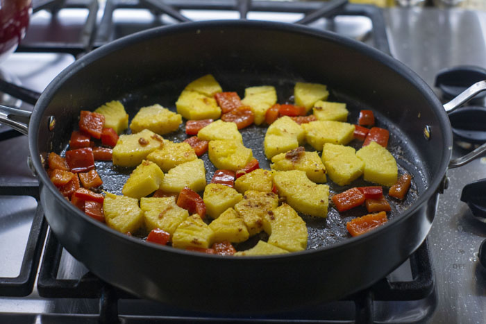 Chopped red bell peppers and chopped pineapple in a large skillet over a gas stovetop
