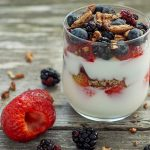 Yogurt in a glass with fruit and chopped nuts on a wooden background with ingredients around it