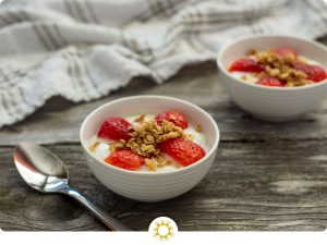 Two small bowls with yogurt and strawberries with granola on a wooden background next to a spoon (with logo overlay)
