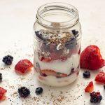 Yogurt parfait in a mason jar on a white background with extra ingredients around it