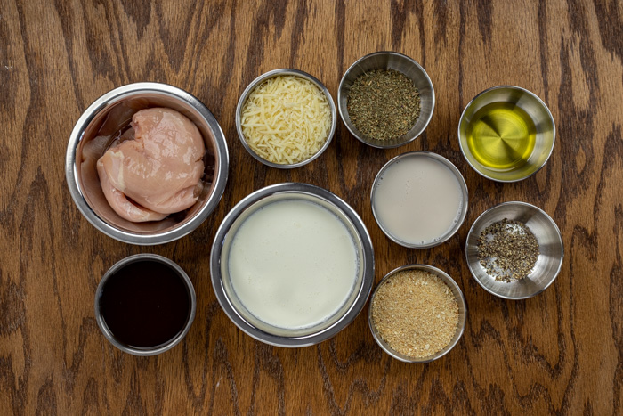 Ingredients for chicken basil cream in stainless steel bowls on a wooden surface