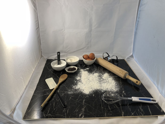 Behind the scenes photo of a marble-topped surface in a white surround lightbox with baking equipment and ingredients on it