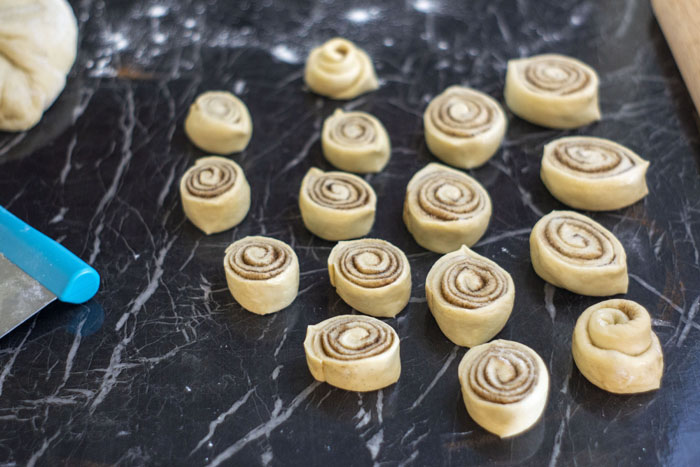 Slices of cinnamon roll on a black marble surface next to a rolling pin, ball of dough, and pastry cutter