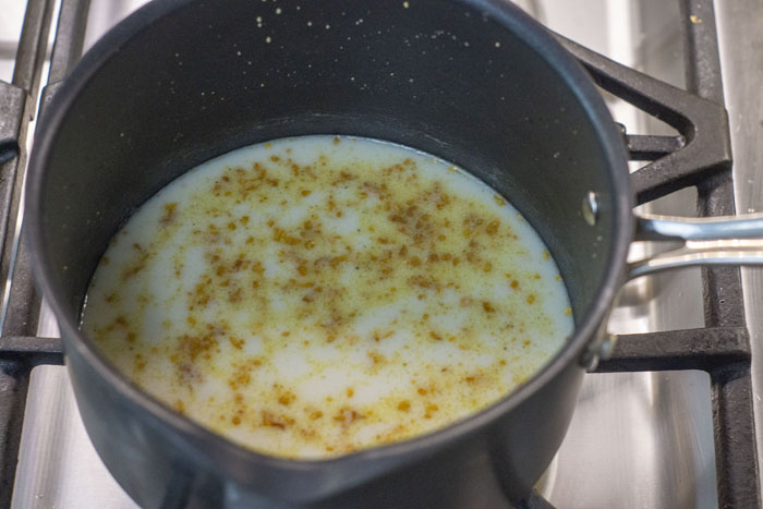 Milk added to roasted garlic and butter in a small saucepan over a gas stovetop