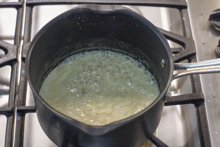 Liquid simmering in a small saucepan on a gas stovetop
