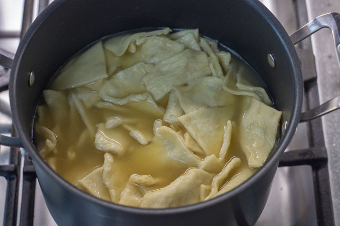 Stockpot full of broth and dumplings over a gas stovetop