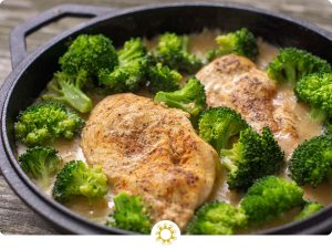 Two cooked and seasoned chicken breasts with chopped broccoli in a cast iron skillet surrounded by garlic cream sauce on a wooden surface (with logo overlay)