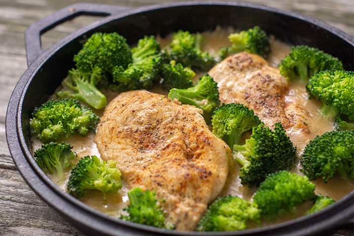Two cooked and seasoned chicken breasts with chopped broccoli in a cast iron skillet surrounded by garlic cream sauce on a wooden surface