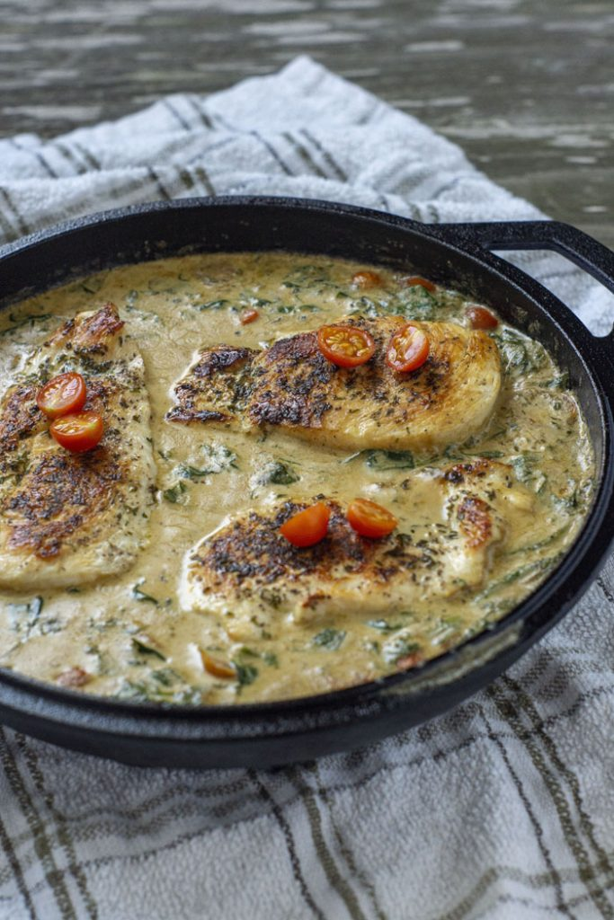 Cooked chicken breasts topped with sliced tomatoes sitting in a cream sauce in a cast iron pan on a white and brown towel (vertical)