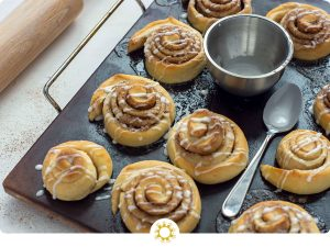 Baked cinnamon rolls on a baking stone with a small bowl of icing and a spoon on the pan on a white surface next to a wooden rolling pin (with logo overlay)