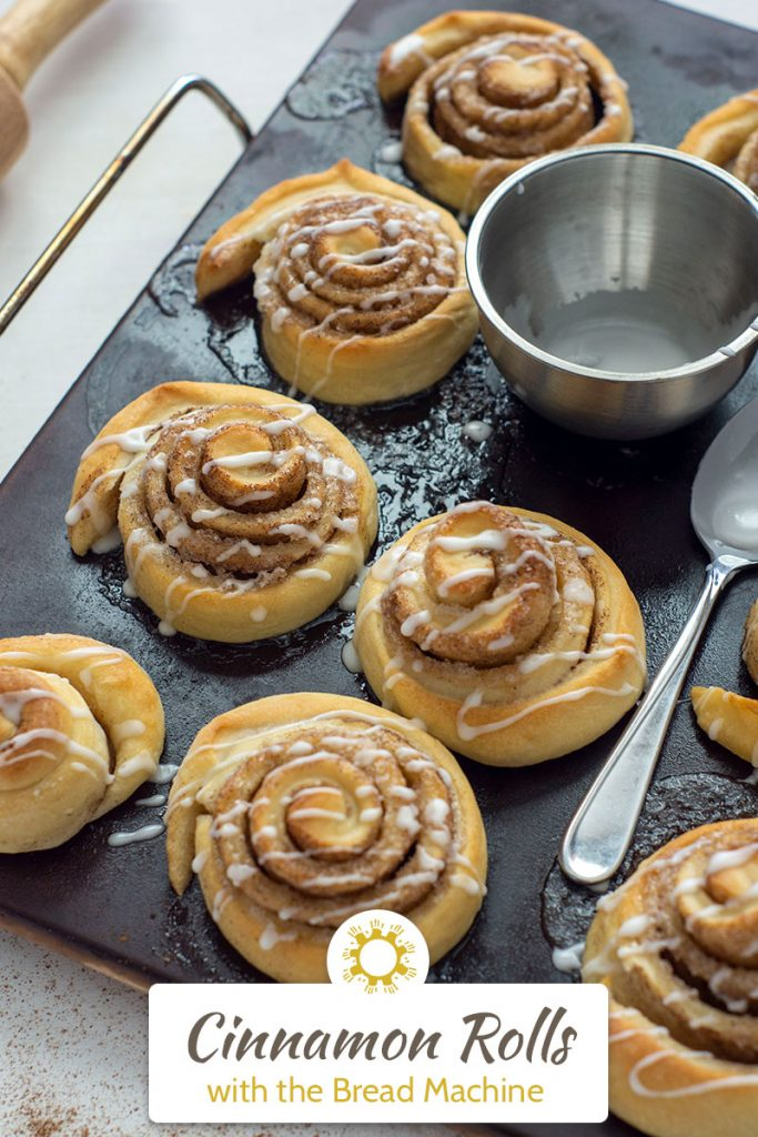 Baked cinnamon rolls on a baking stone with a small bowl of icing and a spoon on the pan on a white surface next to a wooden rolling pin (with title overlay)