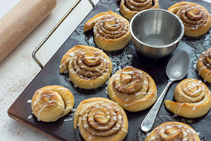 Baked cinnamon rolls on a baking stone with a small bowl of icing and a spoon on the pan on a white surface next to a wooden rolling pin