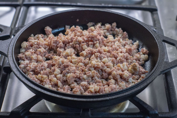 Uncooked corned beef hash in a cast iron skillet over a gas stovetop