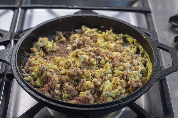 Cooked corned beef hash mixed with scrambled eggs in a cast iron skillet over a gas stovetop
