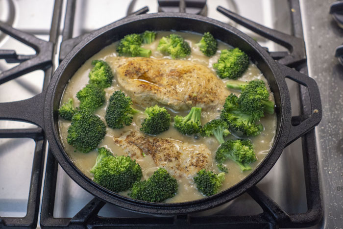 Cooked chicken and chopped broccoli in a cream sauce in a cast iron skillet over a gas stovetop