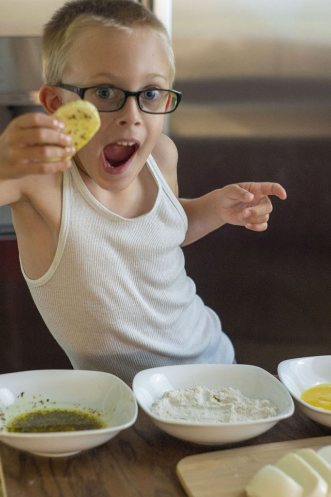 Young boy in glasses holding a piece of mozzarella cheese covered with oil and seasonings over three white bowls with ingredients for making fried mozzarella cakes
