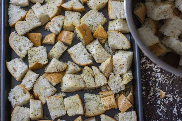 Cut pieces of bread covered in seasonings on a metal baking sheet next to a mixing bowl with more pieces of bread
