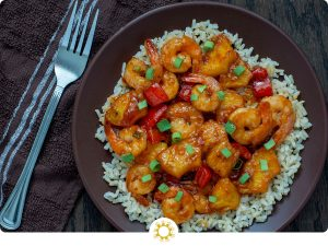 Pineapple shrimp stir-fry over a bed of rice garnished with green onion on a brown plate on a wooden surface with a towel and fork to the left side (with logo overlay)