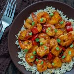 Pineapple shrimp stir-fry over a bed of rice garnished with green onion on a brown plate on a wooden surface with a towel and fork to the left side