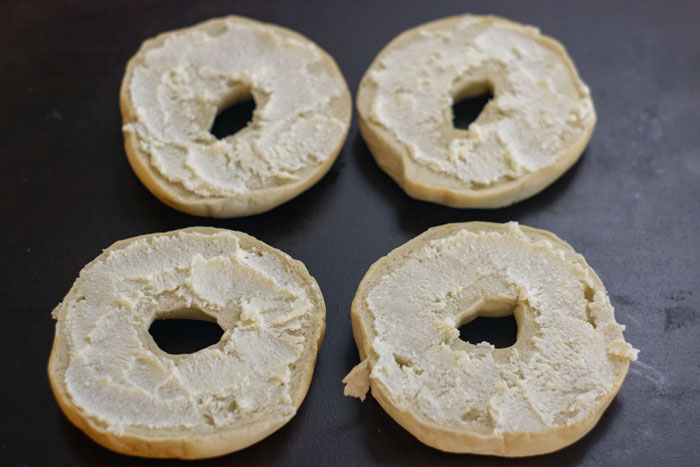 Sliced bagels covered with a layer of ricotta cheese placed on a dark baking stone