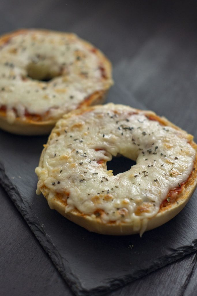 Homemade Pizza Bagels covered with layers of sauce and cheese on a slate serving tray on a dark wooden surface (vertical)