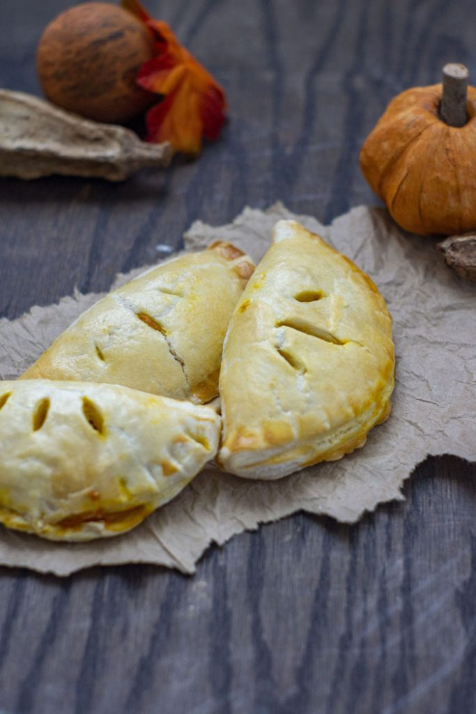 3 pumpkin pasties piled together on a brown paper with fall decorations behind all on a wooden surface (vertical)
