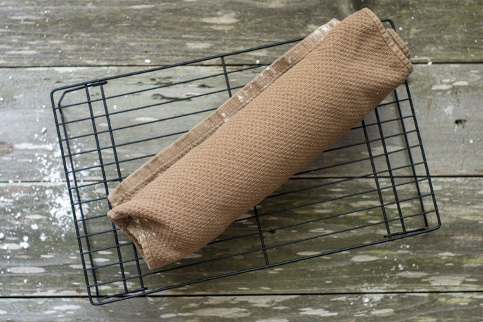 Overhead view of a brown towel rolled around the cake sitting on a wire cooling rack on a wooden surface