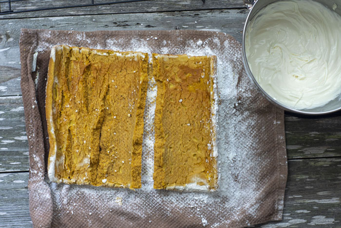 Overhead of pumpkin cake rolled out on a brown towel sprinkled with powdered sugar next to a stainless steel bowl of frosting all on a wooden surface