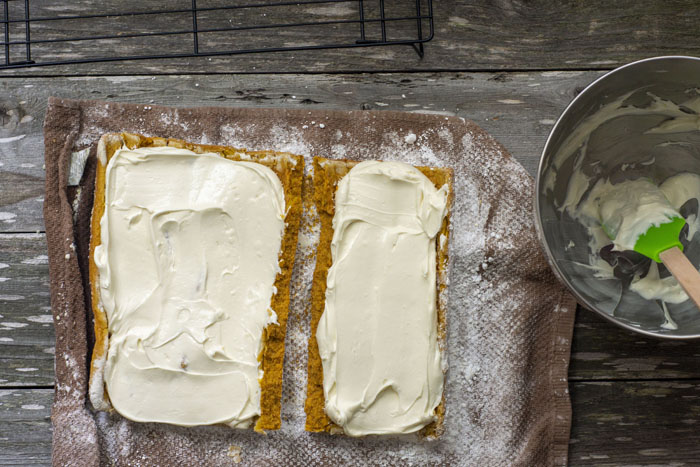 Overhead of pumpkin cake covered in frosting rolled out on a brown towel sprinkled with powdered sugar next to an almost empty stainless steel bowl of frosting all on a wooden surface