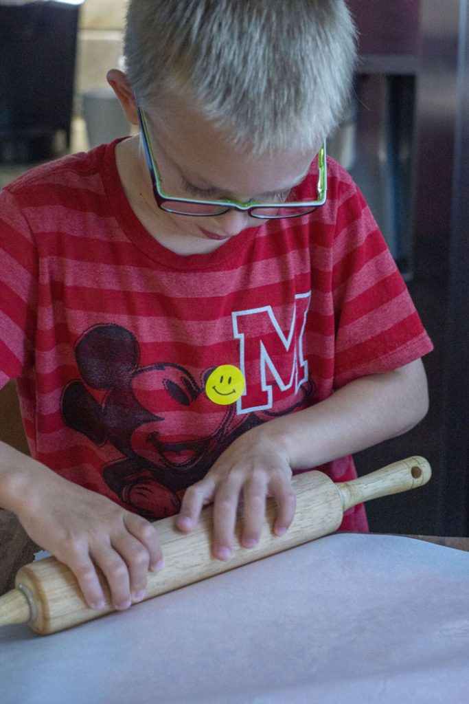Young boy using a rolling pin to flatten orange-colored rice krispies between two pieces of wax paper