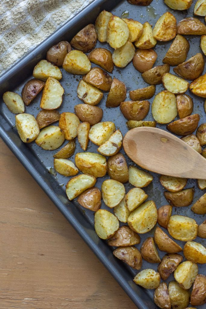 Roasted Potatoes with a wooden spoon on a metal baking sheet next to a tan towel on a light wooden surface (vertical)