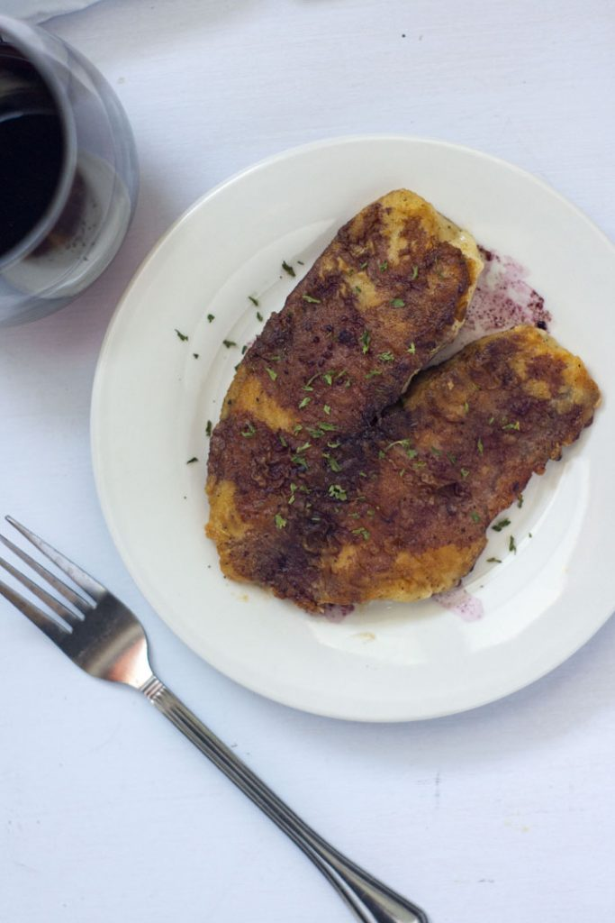 Tilapia with pinot noir sauce on a round white plate next to a fork and a glass of red wine on a white surface (vertical)